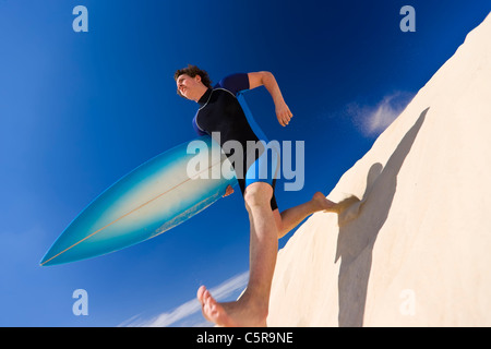 Surfer taking big strides down sand dune to the ocean. - Stock Photo