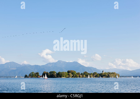 Germany, Bavaria, Chiemgau Alps, Frauenchiemsee, Chiemsee, View of sailing ships on lake near island - Stock Photo