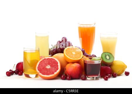 Glasses of fruit juice with fruits on white background. - Stock Photo