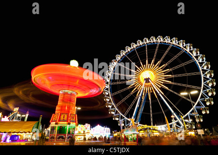Germany, Bavaria, Munich, View of illuminated chairoplane and ferris wheel at night - Stock Photo