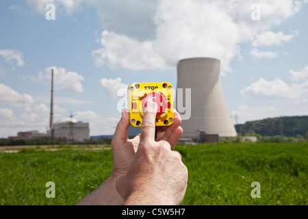 Germany, Bavaria, Unterahrain, Hand of man pressing shut off button near AKW Isar - Stock Photo