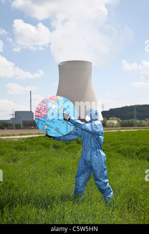 Germany, Bavaria, Man in protective workwear holding globe at AKW Isar - Stock Photo