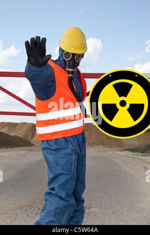 Germany, Man in protective workwear near radioactive warning symbol - Stock Photo