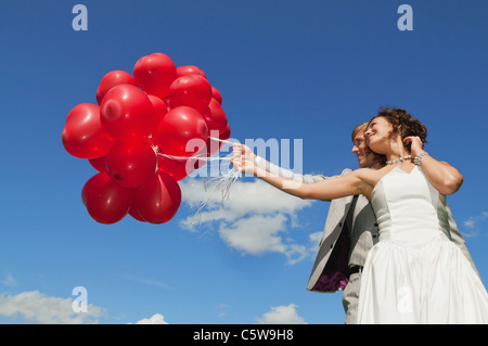 Germany, Bavaria, Bride and groom holding balloons, outdoors, portrait, low angle view - Stock Photo