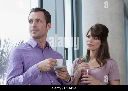 Germany, Cologne, Couple standing in front of window, portrait - Stock Photo