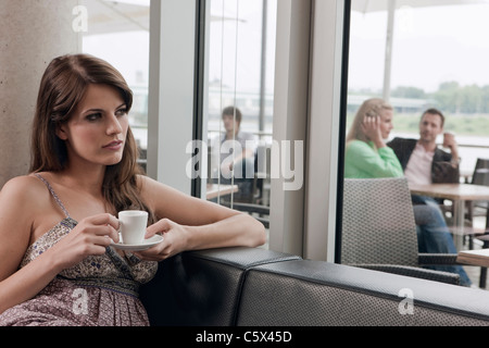 Germany, Cologne, Woman in cafe holding cup of espresso - Stock Photo