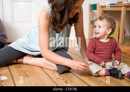 Germany, Berlin, Mother and son (2-3) sitting on wooden floor, laughing, portrait - Stock Photo