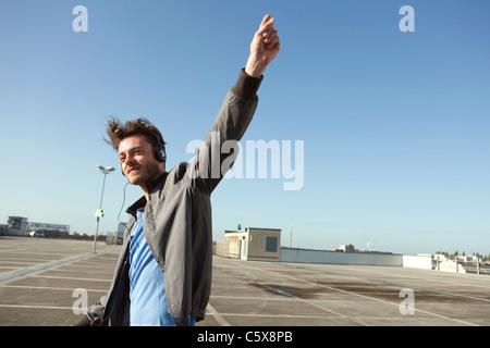 Germany, Berlin, Young man on empty parking level wearing headphones - Stock Photo