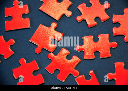 Pieces of a red puzzle on a blue background - Stock Photo