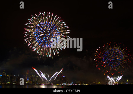 The 35th annual Macy's Fourth of July Fireworks on the Hudson River with the midtown Manhattan skyline in the background - Stock Photo