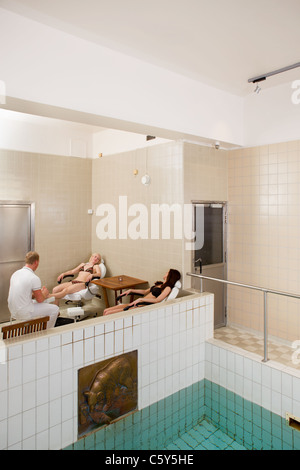A spa interior with two women receiving a pedicure and foot massage in the background - Stock Photo