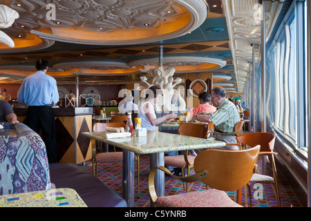 Senior couple eating lunch next to window in Carnival Triumph cruise ship cafeteria - Stock Photo