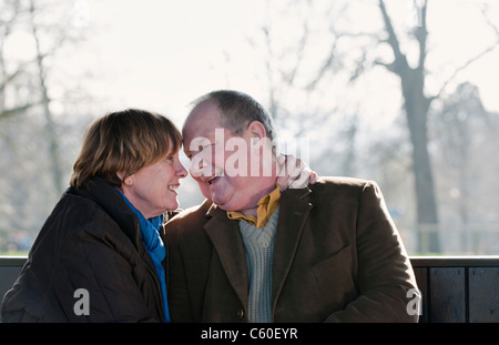 Older couple touching foreheads outdoors - Stock Photo