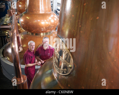 Workers with stills in distillery - Stock Photo