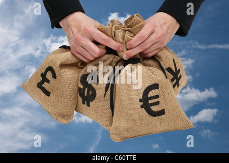four money bags with euro, yen, pound and dollar signs are hand-held - Stock Photo