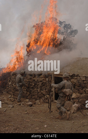 U.S. Army soldiers burn down a Taliban safe house discovered during operations in the Paktika province of Afghanistan. - Stock Photo