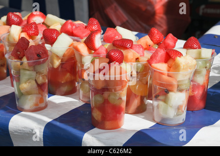 Mixed fresh fruit cocktails for sale in disposable plastic cups on a market stall with blue and white tablecloth - Stock Photo