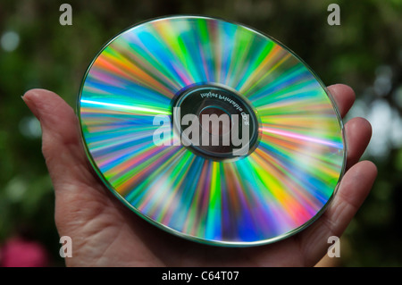 CD / DVD disc disk outdoors reflecting rainbow colors from sunlight - Stock Photo