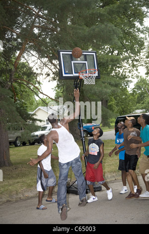 Boys play a pick-up game of street basketball in the Brightmoor neighborhood, Detroit, MI. - Stock Photo