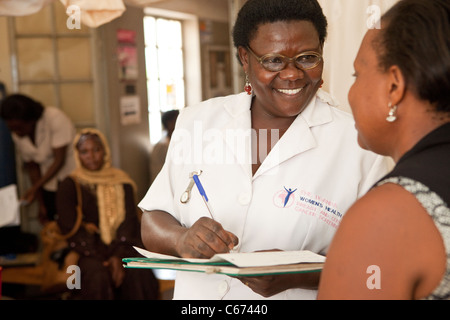 A nurse consults with a patient at a clinic in Kampala, Uganda, East Africa. - Stock Photo