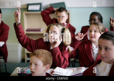 A pupil in a secondary school in the UK puts her hand up during a lesson to answer a question. - Stock Photo
