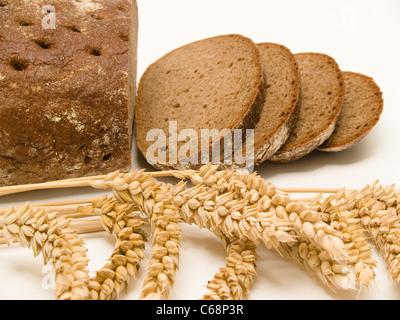 ein angeschittenes Schwarzbrot, davor liegen Weizenähren | a sliced Brown Bread in front are wheat ears - Stock Photo