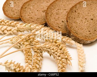 Brotscheiben, daneben liegen Weizenähren | slice of bread, alongside are wheat ears - Stock Photo