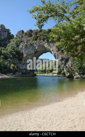 Pont d'Arc rock archway over the Ardeche river Gorges d'Ardeche Gard France with canoes and tourists sunbathing - Stock Photo