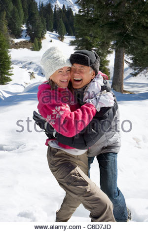 Laughing couple hugging in snowy woods - Stock Photo