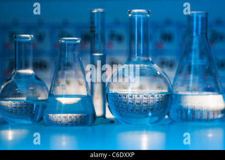 Beakers and flasks with periodic tables in laboratory - Stock Photo