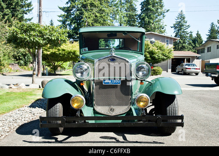 front view restored 1930 vintage Ford Model A car parked in context of suburban driveway bucolic street Edmonds - Stock Photo