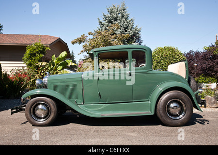 restored classic 1930 green Model A Ford car with open rumble seat parked in context of suburban driveway Edmonds - Stock Photo