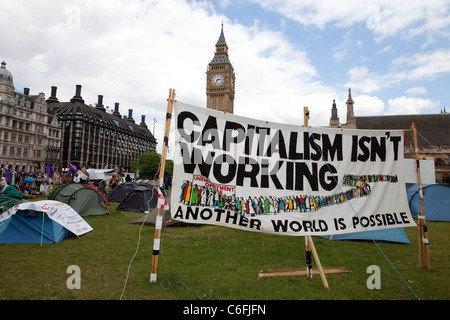 A view of Big Ben and Democracy Village peace camp with tents and anti-capitalism banners. - Stock Photo