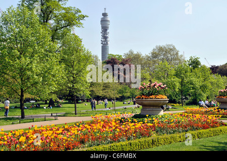 British Telecom BT tower on London skyline with people in Royal Park spring flower gardens in Regents Park London - Stock Photo