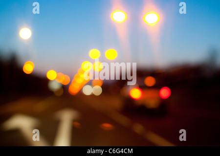 Street lights and car tail lights on a road at dusk - Stock Photo