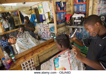Local man having his hair trimmed with an electric trimmer at a barber shop - Stock Photo