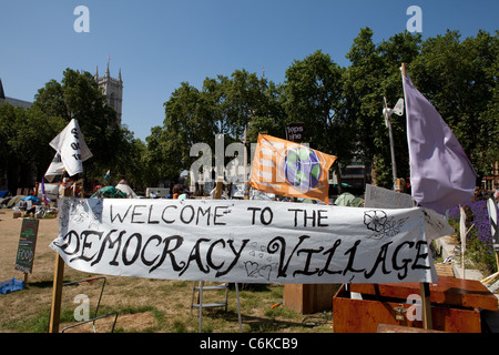 View of Democracy Village with a welcome banner, tents and flags in the background. - Stock Photo