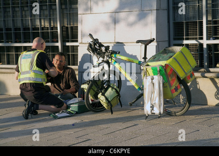 Paramedic on bicycle ambulance attends a patient on a London street, UK - Stock Photo