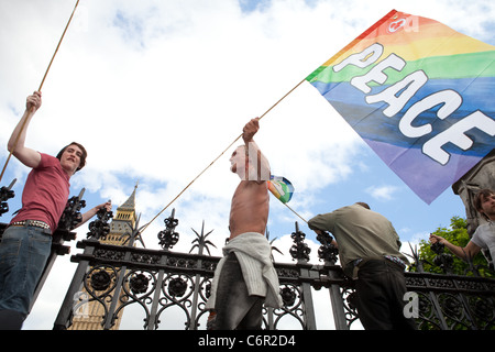 Democracy Village campers hang peace flags on the gates of the Houses of Parliament. - Stock Photo