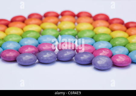 Rainbow smartie pattern on a white background. - Stock Photo