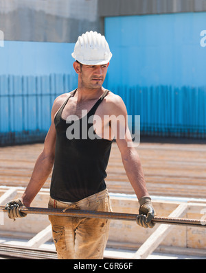 Construction worker carrying reinforcement steel bars - Stock Photo