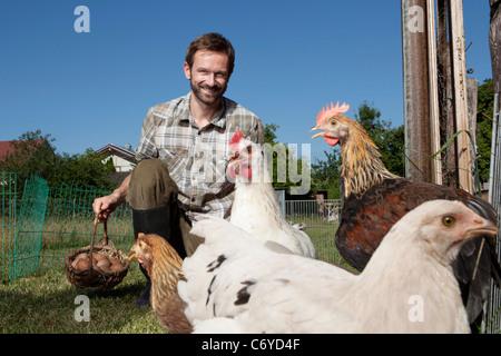 Man feeding chickens outdoors - Stock Photo