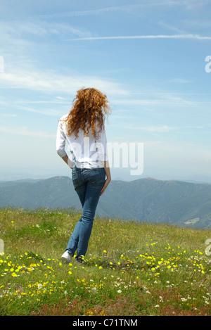 Woman walking through meadow - Stock Photo