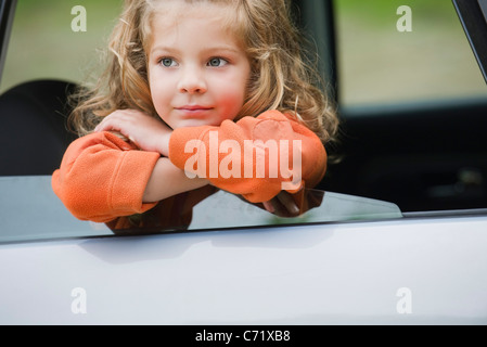 Little girl looking out car window, portrait - Stock Photo