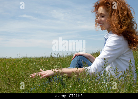Woman sitting in meadow, running fingers through grass - Stock Photo