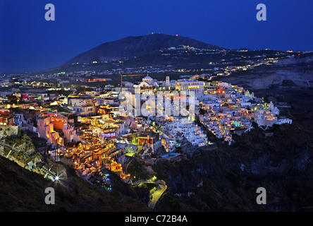 Night view of Fira village, the 'capital' of Santorini island, hanging over the caldera. Cyclades, Greece - Stock Photo