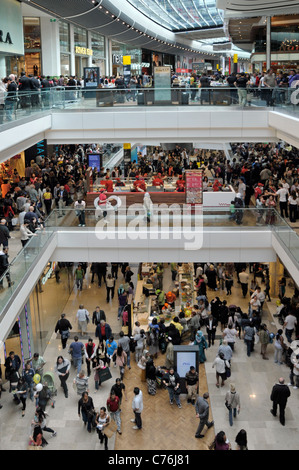 View from above looking down on busy crowd of people in shopping mall interior at Stratford City Westfield shopping - Stock Photo