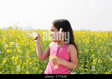Young girl making bubbles in a field - Stock Photo