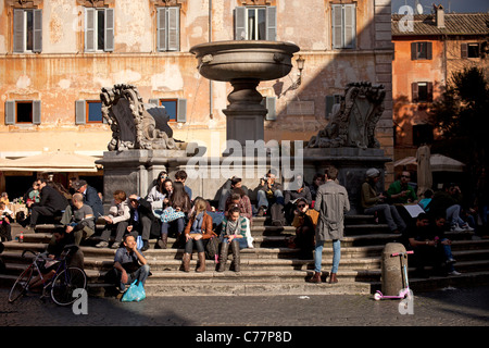 youth sitting at the fountain on Piazza Santa Maria in Trastevere, Rome, Italy - Stock Photo