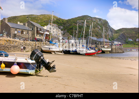 Low tide at Barmouth harour, colorful yachts roped to harbour wall, tourists, old buildings and rocky hillside in - Stock Photo
